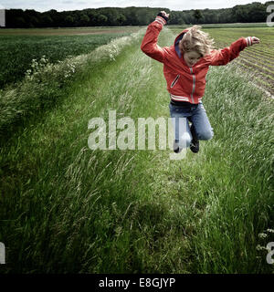 Ragazzo di saltare in un campo Foto Stock