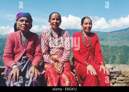 Ritratto di tre donne locali nepalesi seduti su un muro in un villaggio di montagna, il Nepal Foto Stock