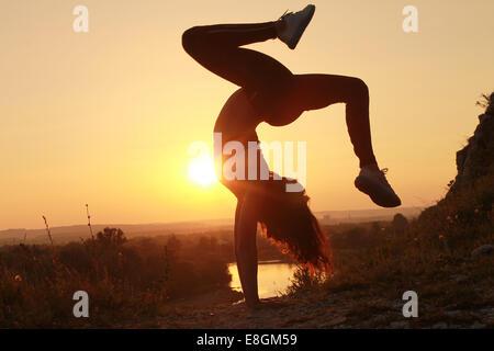 Giovane donna facendo handstand al tramonto Foto Stock