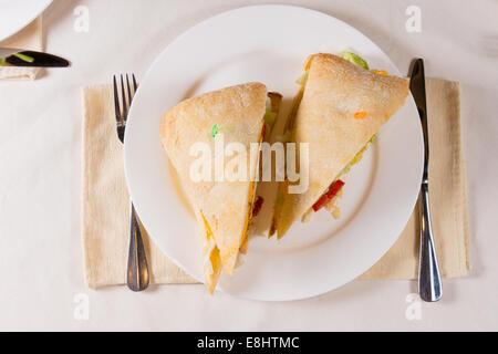 Sovraccarico di panino sulla piazza Ciabatta Bun sulla piastra al ristorante posto impostazione Foto Stock