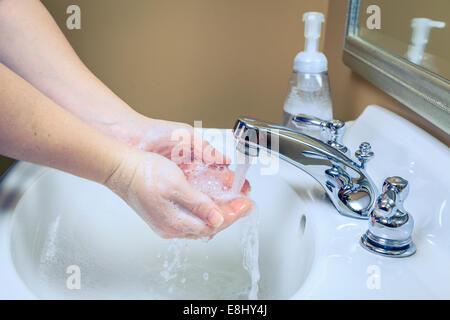 La donna è di lavarsi le mani con sapone in un lavandino del bagno Foto Stock