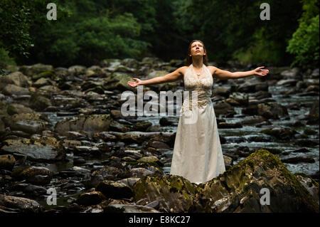 """Cestino il vestito: un """"sposa' che indossa il suo abito da sposa in piedi in un fiume con le braccia aperte adorare Foto Stock"""