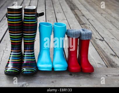 Tre coppie di un colorato stivali da pioggia. Concetto di famiglia Foto Stock