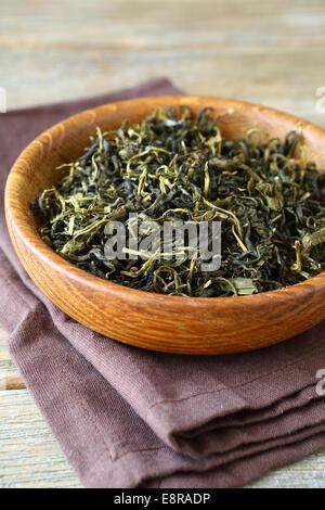 Le foglie di tè in una ciotola di legno, sul tovagliolo Foto Stock