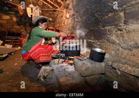 Giovane donna per la cottura sul fuoco aperto nella sua cucina tradizionale, Unione Potrero, Quispillacta, Ayacucho, Foto Stock