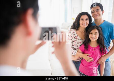 Famiglia di origine ispanica tenendo cellulare fotografia in salotto
