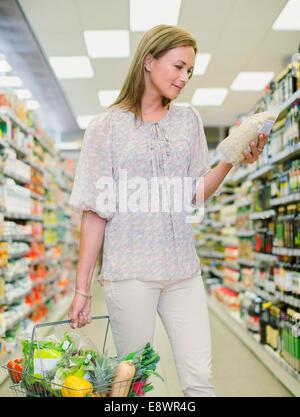 Donna shopping nel negozio di alimentari Foto Stock