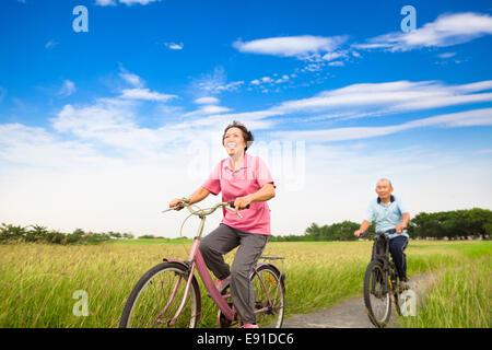 Felice Asian anziani anziani matura mountain bike in fattoria con cielo blu sullo sfondo Foto Stock