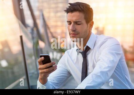 Imprenditore tramite telefono cellulare Foto Stock