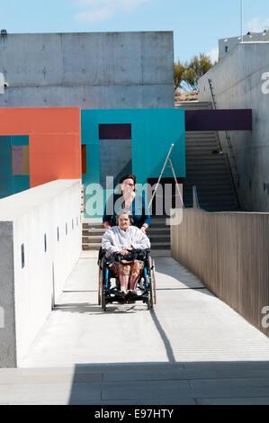 Una signora anziana viene spinto in alto un calcestruzzo disabili rampa di accesso in sedia a rotelle dal suo accompagnatore Foto Stock