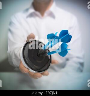 Uomo di trattenimento sul bersaglio nero con tre blu freccette di colpire il centro. Concetto di immagine per immagine Foto Stock