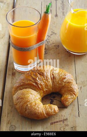 Millefoglie croccante golden croissant giacente su un vecchio trama da tavolo in legno con un bicchiere di succo Foto Stock