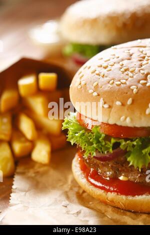 Due hamburger e patatine fritte con sesamo bun su carta marrone. messa a fuoco selettiva Foto Stock