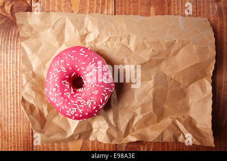 Vista aerea di una fragola rosa ciambella con spruzza su una lastra di accartocciata grungy carta marrone con copyspace Foto Stock