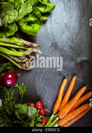 Verdura fresca cornice o telaio su ardesia testurizzata con copyspace per il tuo testo con fattoria fresco mazzetti di asparagi spears, carote, il ravanello di spinaci e barbabietole