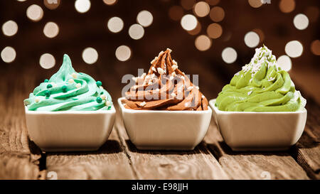 Coloratissima fila di tre differenti frozen yogurt dessert in blu, marrone e verde guarnito con dadi e perle di Foto Stock