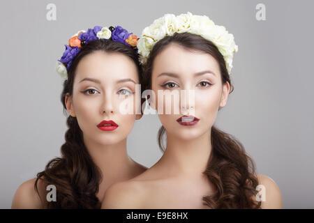 Eleganza. Due donne con ghirlande di fiori. Fantasy Foto Stock
