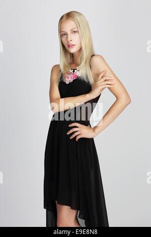Dama sofisticata in nero setoso abito da sera con garbo in posa