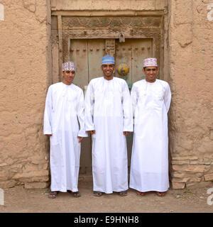 Tre giovani Omani uomini in abito tradizionale presso le rovine di Birkat Al Mouz in Nizwa area del Sultanato di Foto Stock