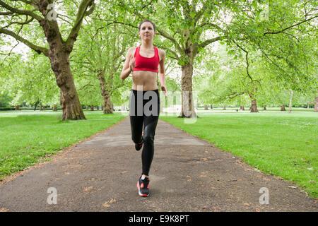 Lunghezza completa di montare la giovane donna a fare jogging nel parco