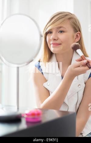 Applicando la ragazza trucco nella parte anteriore dello specchio a casa Foto Stock