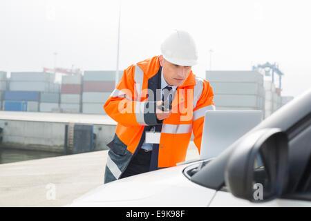 Uomo di mezza età parlando su un walkie-talkie durante l'utilizzo di laptop in cantiere di spedizione Foto Stock