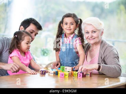 Felice tre generazioni la famiglia gioca con blocchi di alfabeto a casa Foto Stock