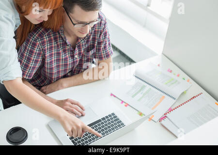 Azienda giovane utilizzando computer portatile in ufficio creativo Foto Stock