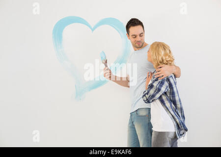 Amare mid-adulto giovane con cuore dipinta sulla parete Foto Stock