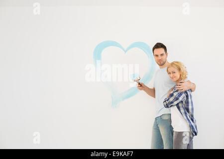 Ritratto di amare a metà adulto giovane con cuore dipinta sulla parete Foto Stock