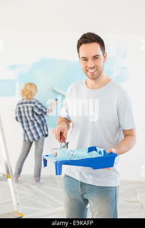 Ritratto di uomo con rullo di vernice e il vassoio con donna muro dipinto in background Foto Stock