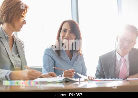 Imprenditrice sorridente con i colleghi in sala riunioni Foto Stock