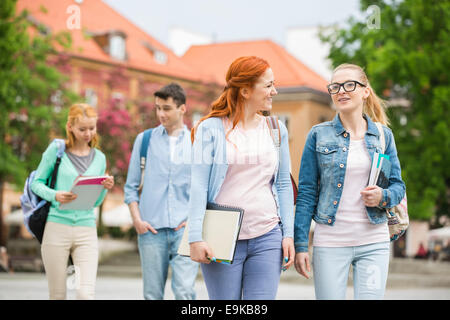 Giovani amici universitari camminando sulla strada