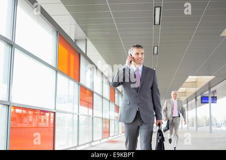 Persone di mezza età imprenditore su chiamata mentre si cammina nella stazione ferroviaria Foto Stock
