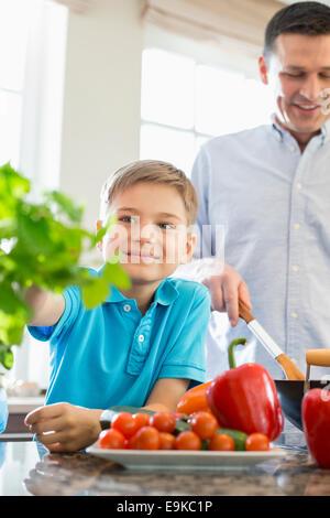 Ragazzo sorridente toccando houseplant con padre preparare il cibo in cucina Foto Stock