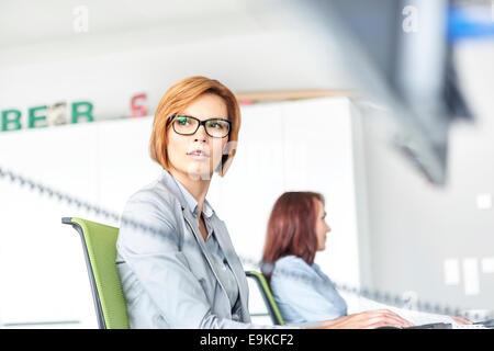 Giovane imprenditrice lavorando sul computer con il collega in background in ufficio Foto Stock