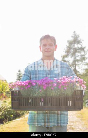 Ritratto di uomo che porta cassa con vasi di fiori nel giardino Foto Stock