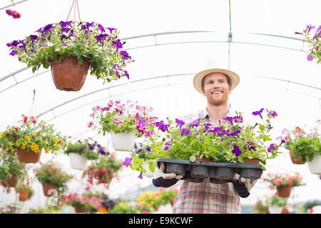 Happy gardener holding fioriere in cassa in serra Foto Stock