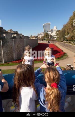 Torre di Londra papaveri memorial - i bambini in visita con le loro bambole guardando i papaveri nel fossato, London Foto Stock