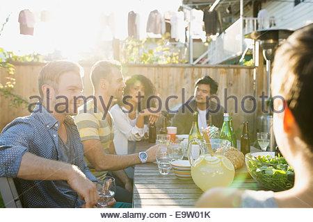 Gli amici di mangiare e bere a backyard barbecue Foto Stock