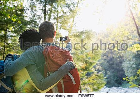 Giovane tenendo selfie nella soleggiata boschi Foto Stock