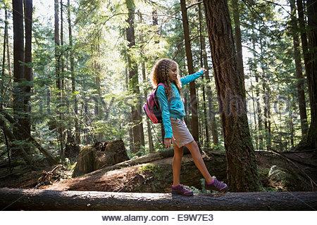 Ragazza camminare su albero caduto nei boschi Foto Stock