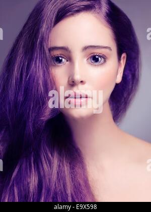 Carino giovane donna faccia con grandi occhi tristi e lunghi capelli viola ritoccata in giapponese in stile anime Foto Stock