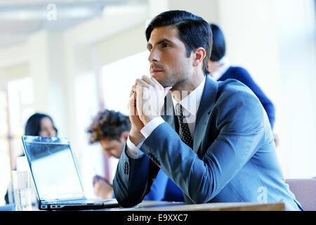 Ritratto di un imprenditore pensieroso seduto al tavolo in ufficio Foto Stock