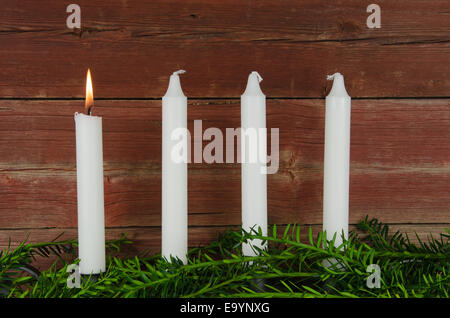 Quattro candele di avvento con uno di loro che brucia a uno sfondo di vecchio granaio rosso parete Foto Stock