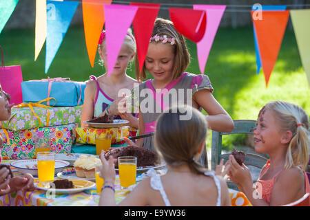 La ragazza che serve gli amici torta di compleanno Foto Stock