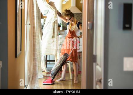 Giovane donna di aspirare con verde di prodotti per la pulizia Foto Stock