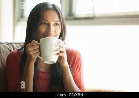 Donna con il caffè a casa Foto Stock