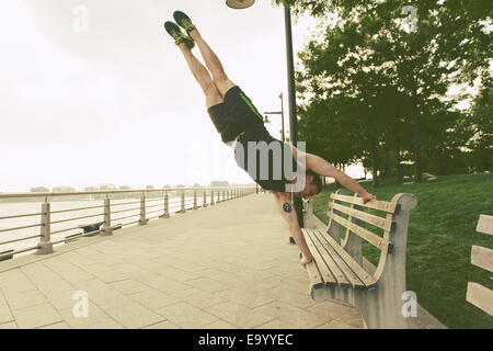 Giovane uomo facendo handstand su Riverside park panchina Foto Stock