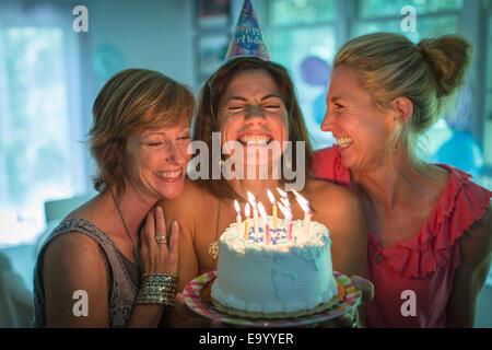 Donna matura holding torta di compleanno, rendendo desiderate mentre due amici a guardare Foto Stock